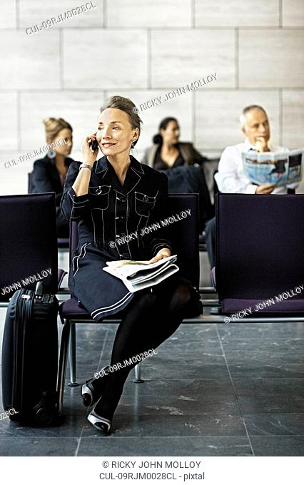 Woman with a suitcase, on the phone