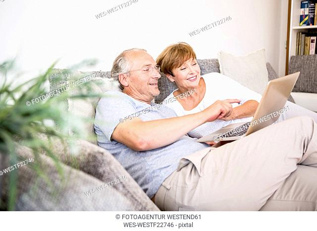 Senior couple at home sitting on couch using laptop