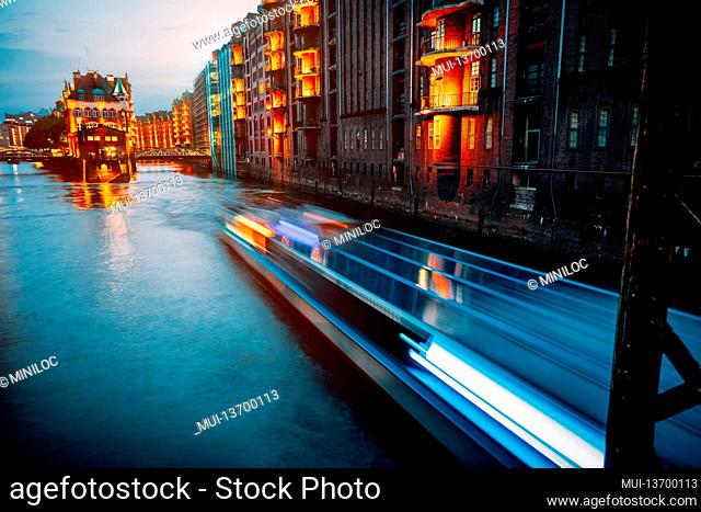 A colorfully illuminated boat cruising on the Wandrahmsfleet at night. The Warehouse District in Hamburg, Germany. The district located within the HafenCity...