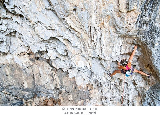 Woman climber climbing a 7a route at Crazy Horse Buttress close to Chiang Mai, Thailand