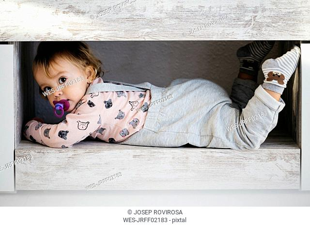 Portrait of baby girl with pacifier hiding at home