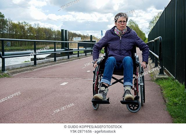 Tilburg, Netherlands. Female multiple sclerosis patient dealing with her condition by on and off using a wheelchair to get along