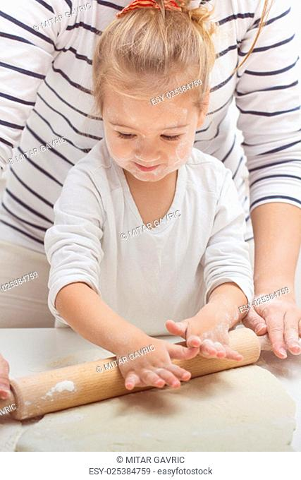 Cute little girl with her mother kneading dough at home