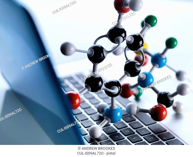 Molecular model sitting on top of lap top computer keyboard to illustrate science education and computer aided research