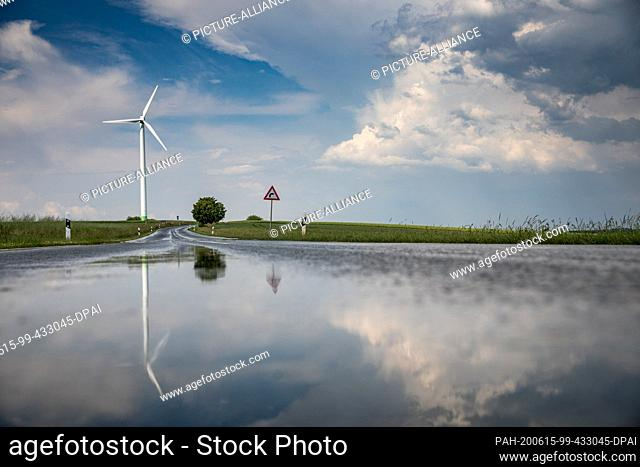 13 June 2020, Saxony, Waldenburg: The landscape is reflected in the wet country road after a rain shower. Photo: Jan Woitas/dpa-Zentralbild/ZB
