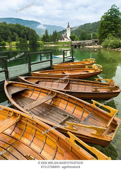 Lake Bohinj (Bohinjsko jezero), Triglav National Park, Upper Carniola, Slovenia. Rowing boats for rent. The church of St