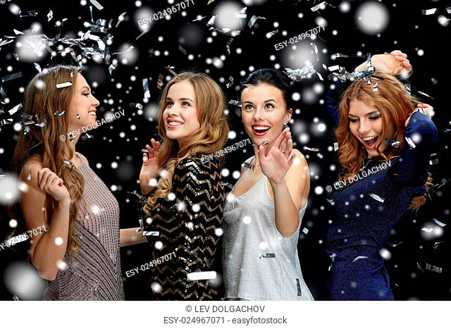 new year party, christmas, winter holidays and people concept - happy young women dancing over black background with snow