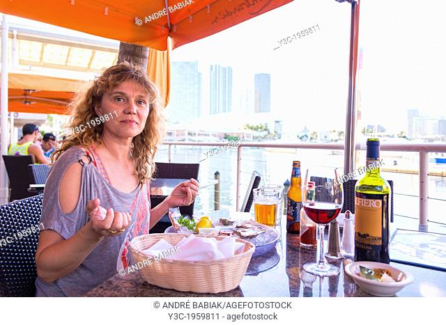 Caucasian woman of 45 years eating fresh raw oysters, Port of Miami, Florida, USA