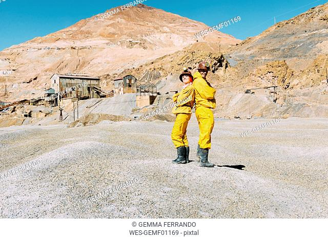 Bolivia, Potosi, two tourists wearing protective clothing standing back to back in front of Cerro Rico