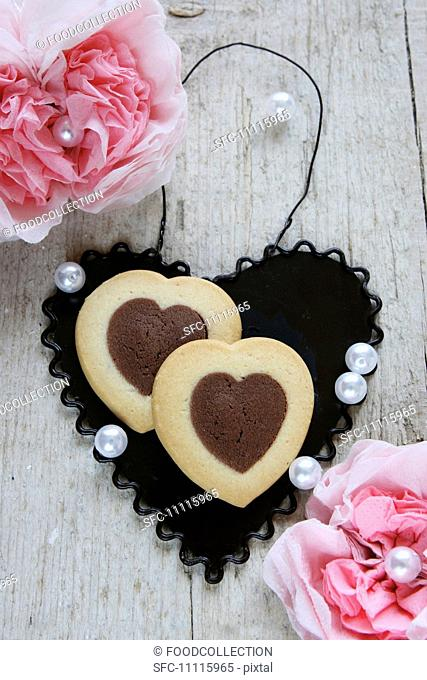 Bi-coloured heart-shaped biscuits on a black metal heart between paper carnations