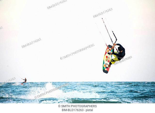 Man kiteboarding over ocean waves