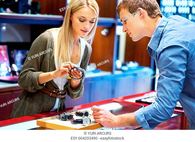 Beautiful young saleslady showing a wristwatch to a male customer