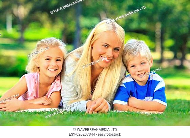 Mother with her children lying down in the park