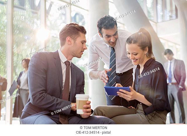 Business people with coffee using digital tablet, talking in office lobby
