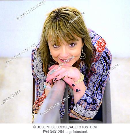 A 51 year old woman smiling at the camera