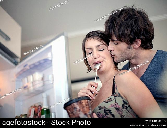 Young man kissing girlfriend eating ice cream in kitchen at home