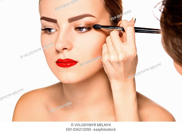 Beautiful female eyes with make-up and brush on white. Makeup artist working process