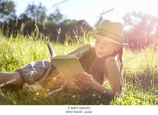 A young girl in a straw hat lying on the grass reading a book