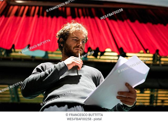 Portrait of pensive man standing on stage of theatre looking at script