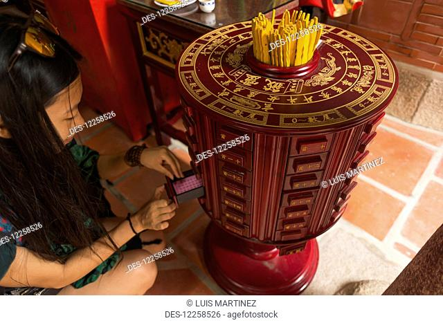 Chinese young woman trying the traditional roll of fortune in a Buddhist temple; Shanzidou, Kinmen Island, Taiwan