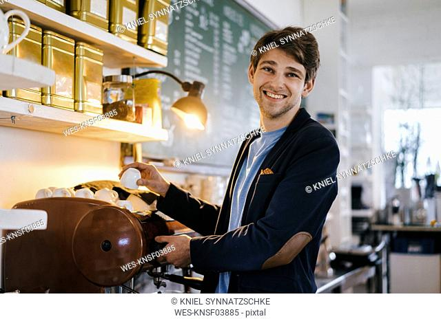 Portrait of smiling man in a cafe holding cup