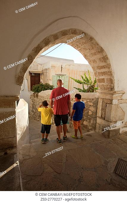 Man with the children at a passageway in the old town Chora, Naxos, Cyclades Islands, Greek Islands, Greece, Europe