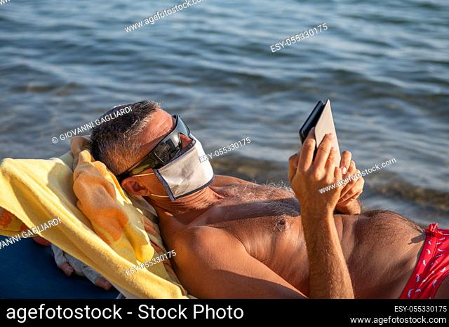 Man wearing mask and reading tablet on the beach in covid times