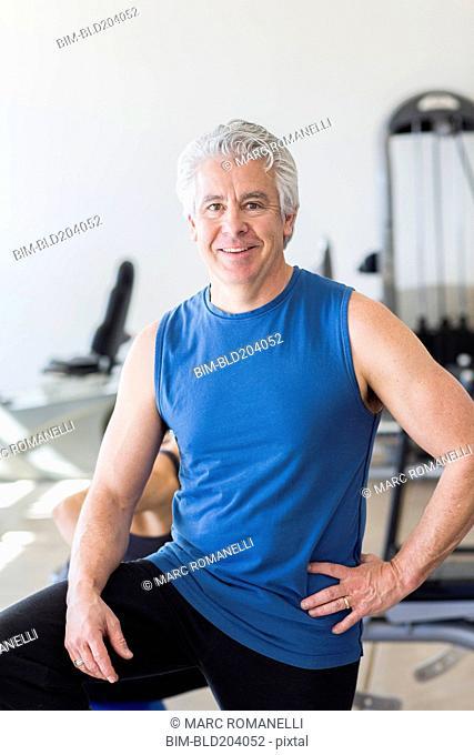 Older Hispanic man smiling in gym
