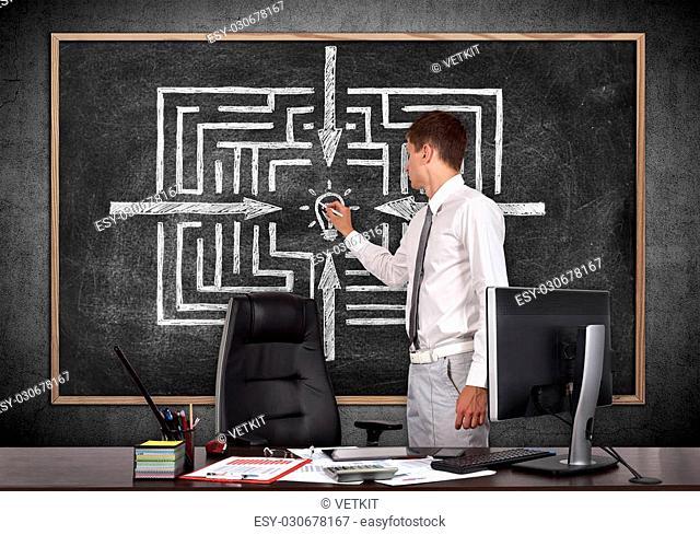businessman in office drawing labyrinth on blackboard
