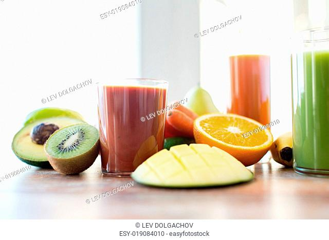 healthy eating, food and diet concept- close up of fresh juice glass and fruits on table