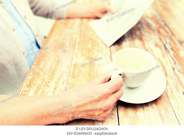 age, leisure and people concept - close up of senior woman drinking coffee and reading newspaper at home