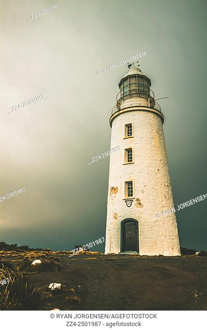 Old style Australian landmarks scene of a historic coastal tower built in 1836 with grey sky copy-space. Cape Bruny Lighthouse, Tasmania, Australia