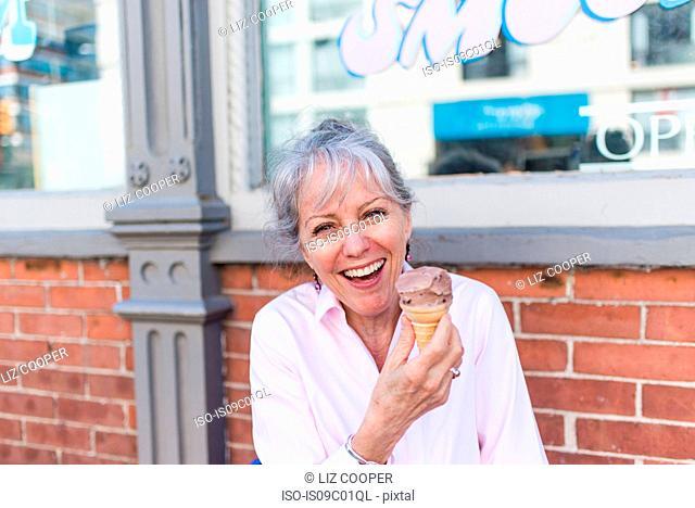 Senior woman sitting on sidewalk with chocolate ice cream cone, portrait
