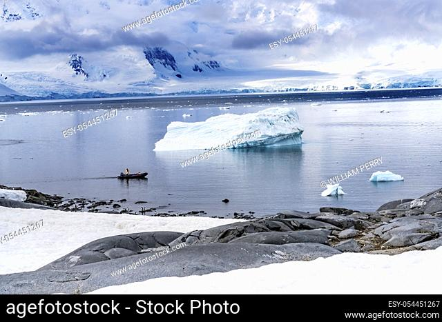 Boat Iceberg Snow Mountains Blue Glaciers Damoy Point Antarctic Peninsula Antarctica. Glacier ice blue because air squeezed out of snow