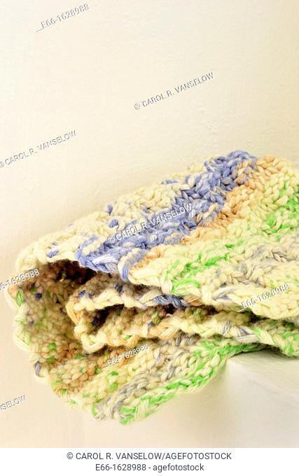Hand knit washcloth on shelf by window, close up