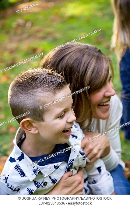 Lifestyle portrait of a young mom laughing and playing with her son at a nature park in Oregon