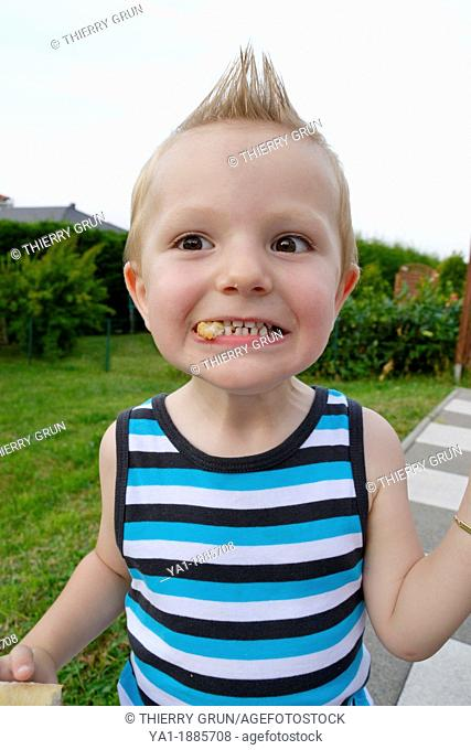 2 years boy making grimace with peace of bred in mouth, France
