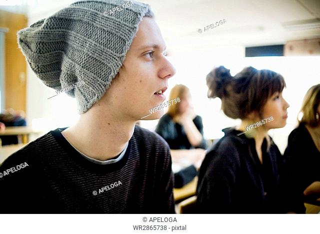 Young man looking away while sitting with female friends in classroom