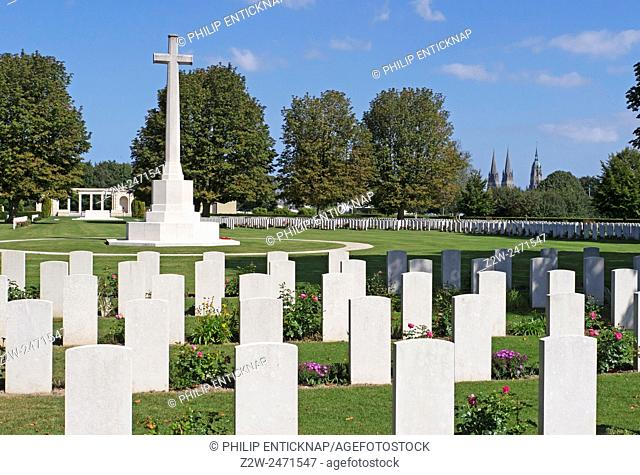 War Graves and Memorial Cross with Bayeux Catherdral in distance. Bayeux War Cemetery is the largest Commonwealth cemetery of the Second World War in France and...