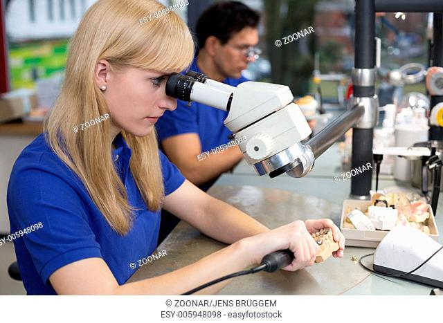 Technician working on dental prosthesis under a microscope
