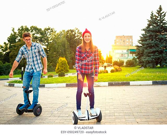 A young couple riding hoverboard - electrical scooter, personal eco transport, gyro scooter, smart balance wheel. New modern technologies
