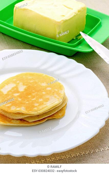 On a white plate stack of pancakes and butter