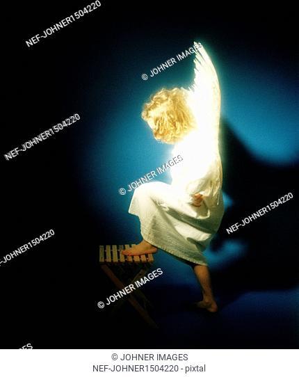 Studio shot of child wearing angel costume moving up on stool