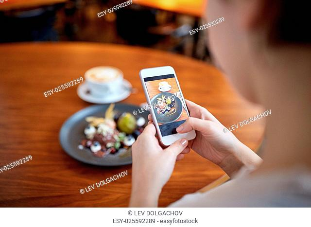 food, new nordic cuisine, technology and people concept - woman with smartphone photographing chocolate ice cream dessert with blueberry kissel