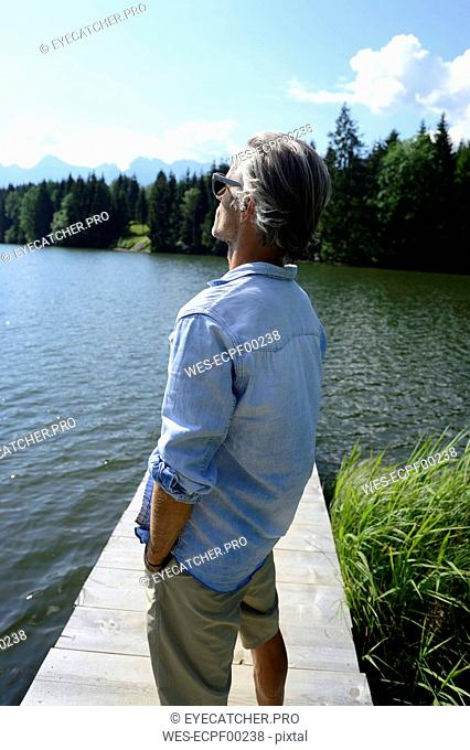 Germany, Mittenwald, mature man standing on jetty at lake relaxing