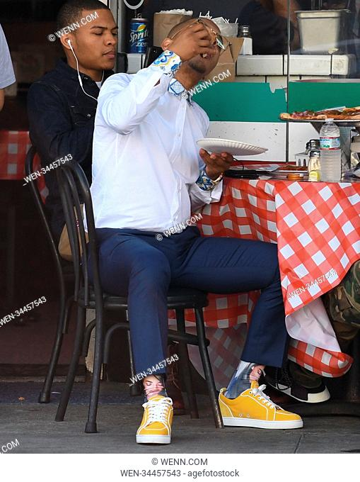 Hip-hop artist T.I. enjoys a slice of pizza at a restaurant with his friends Featuring: T.I., TI Where: Beverly Hills, California