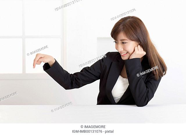 Young business woman pointing down with hand on chin