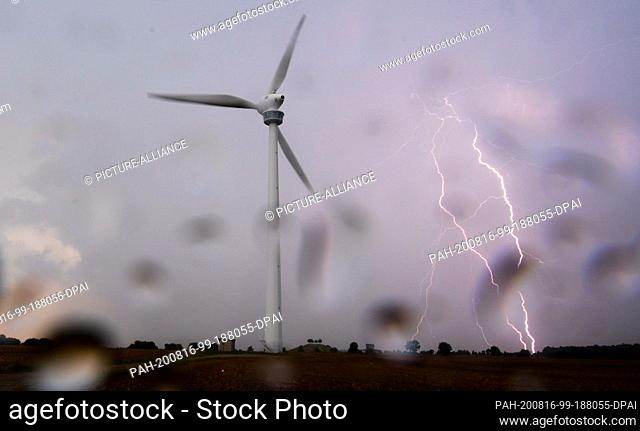 16 August 2020, Lower Saxony, Hanover: A lightning bolt strikes on the horizon behind a wind turbine in the Hannover region - photographed through a window pane...
