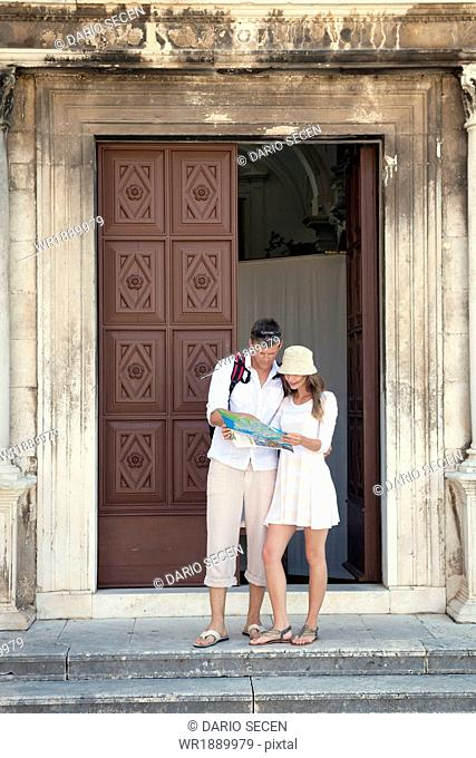 Young couple in front of church, reading a map, Zadar, Croatia