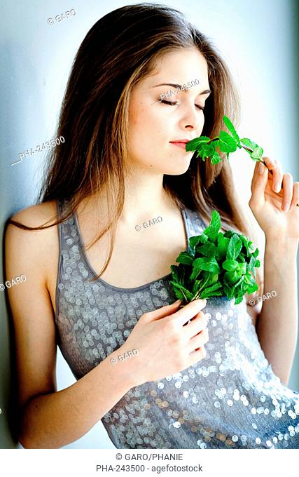 Woman smelling mint leaves Mentha sp.